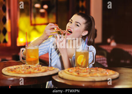 a young pretty girl eating pizza and drinking beer or a beer citrus cocktail on the background of a bar or pizzeria. - Stock Photo