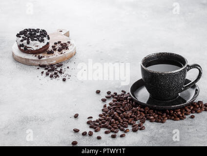 Black coffee cup with saucer and doughnut with black cookies on stone kitchen table background. Space for text. - Stock Photo