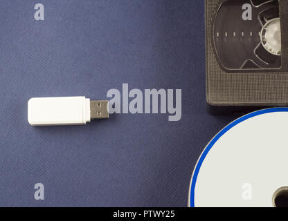 Flash drive on a blue background discs and video cassette - Stock Photo