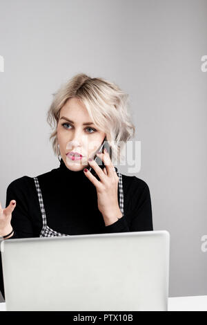 Attractive young women in conversation on a mobile phone in front of a laptop computer serious and concentrating. - Stock Photo