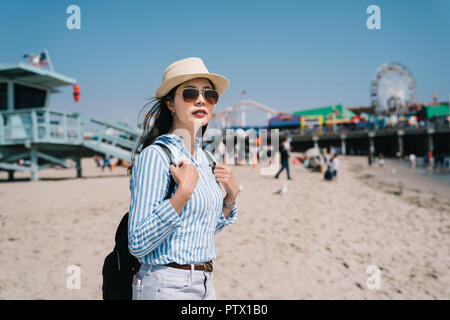 a pretty female tourist relaxing standing next to lifeguard station and seeing the view of the beach - Stock Photo
