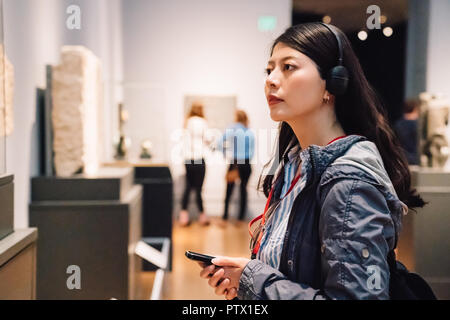 an elegant lady in the exhibition, wearing earphone to hear the voice guide - Stock Photo
