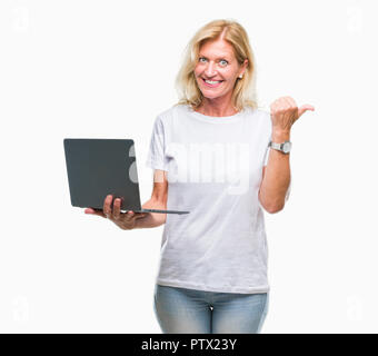 Middle age blonde woman using computer laptop over isolated background pointing and showing with thumb up to the side with happy face smiling - Stock Photo