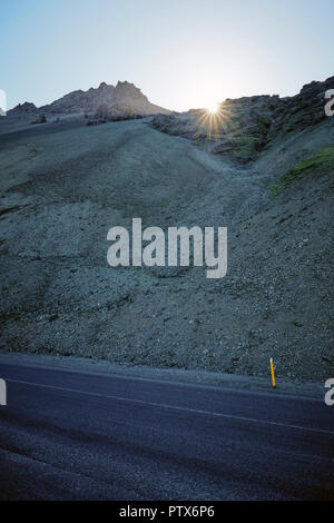 The empty Iceland ring road route 1 cutting through the barren volcanic landscape of south east Iceland. - Stock Photo