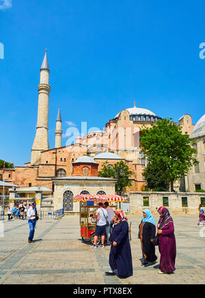 Istanbul, Turkey - July 10, 2018. Muslim women and tourists walking in front of the Hagia Sophia mosque at daylight, and a Corn cobs stall in the fore - Stock Photo