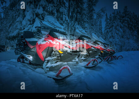 Polar night in Lapland, Finland. Red snowmobiles are ready for adventure ride. Vehicles parked in line near beautiful forest. Heavy snow. Winter seaso - Stock Photo
