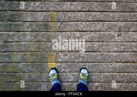 Socked Slippered Feet On Stone Pavement - Stock Photo