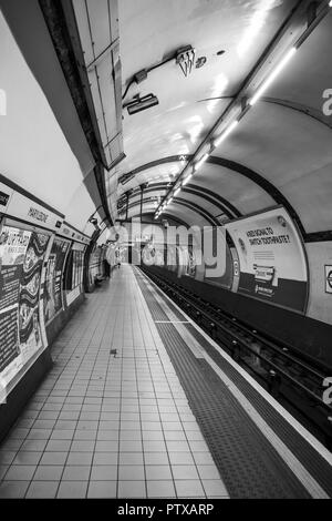 London Tube station; black & white shot of deserted platform/ rail line at London's Marylebone underground station. Solitary figure waits in distance. - Stock Photo