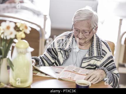 Altenheim, Seniorin liest Zeitung (model-released) - Stock Photo