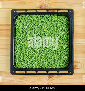 green peas in glass bowl on white table - Stock Photo