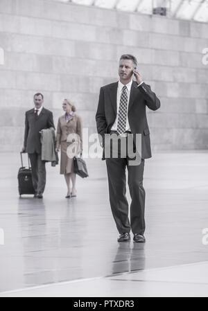 Zwei Maenner und eine Frau gehen durch grosse Halle, ein Mann mit Handy (model-released) - Stock Photo