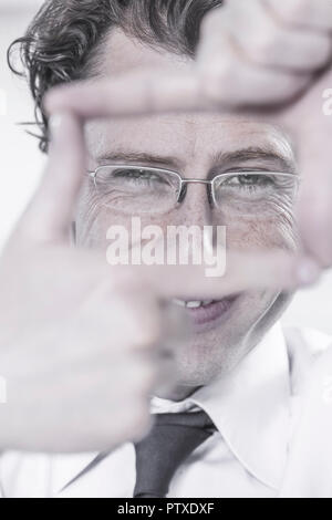 Mann zeigt mit den Fingern Rahmen an, Portraet (model-released) - Stock Photo