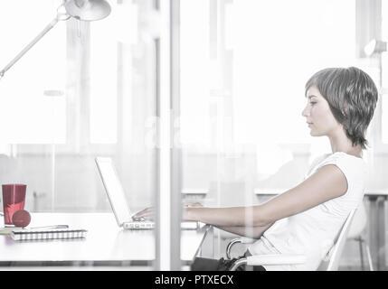 Junge Frau arbeitet mit Notebook, im Buero (model-released) - Stock Photo