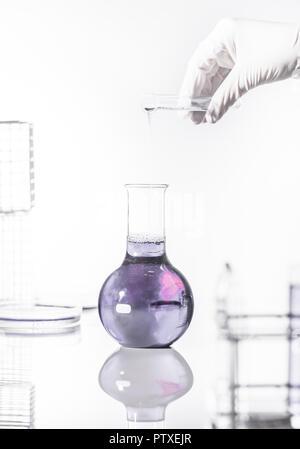 Blaue Fluessigkeit wird von Reagenzglas in Glaskolben gefuellt (model-released) - Stock Photo