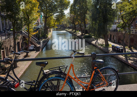 Utrecht, Netherlands - September 27, 2018: Canoeing on the canal in the historical center of Utrecht in autumn seen from a bridge with parked bicycles - Stock Photo