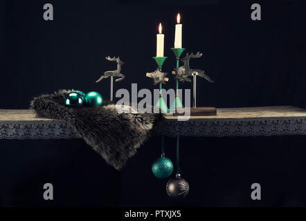 Christmas decoration elements in warm turquoise tones against a dark background. In addition to turquoise, dark brown, wood, fur and old silver create - Stock Photo