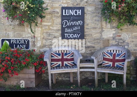 Union jack cushions on wooden outdoor seating - Stock Photo