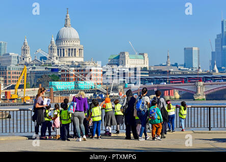 Group of primary school children on the South Bank, looking towards St Paul's Cathedral, London, England, UK. - Stock Photo