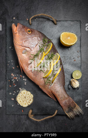 Freshly marinated raw Red snapper fish with lemon slices, garlic and rosemary herbs, on dark background. Vertical composition - Stock Photo