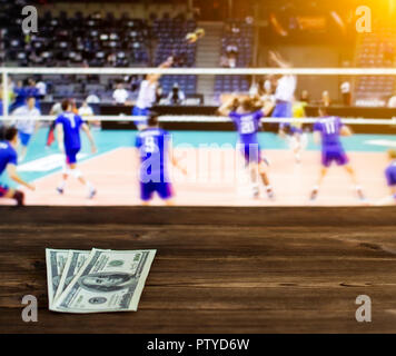 Money dollars on the background of a TV on which show volleyball, sports betting, dollars - Stock Photo