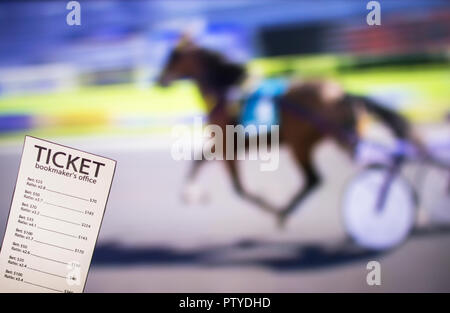 Bookmaker ticket on the background of the TV, which shows sport trotting, sports betting, bookmaker - Stock Photo