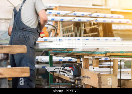 Production of pvc windows, a man collects a pvc window, a screwdriver, worker - Stock Photo