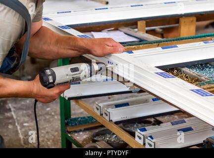 Production of pvc windows, a man screws a screwdriver into a pvc window, close-up, windows pvc - Stock Photo