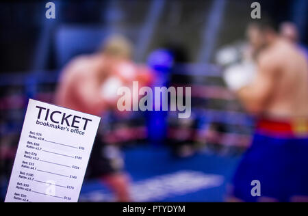 Bookmaker ticket on the background of the TV on which show boxing, sports betting, ring - Stock Photo