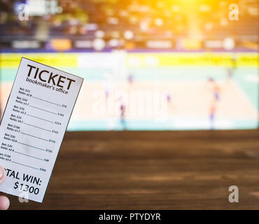 bookmaker ticket on the background of a TV on which show volleyball, sports betting, volleyball - Stock Photo