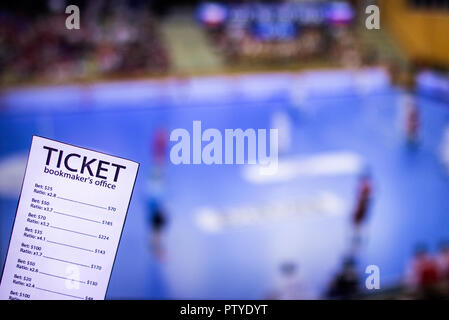 Bookmaker ticket on the background of the TV on which show handball, sports betting, handball - Stock Photo
