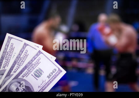 Money dollars against the background of the TV on which show boxing, pugilism - Stock Photo