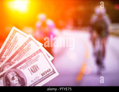 Money dollars on the background of a TV showing cycling, sports betting, cyclotourism - Stock Photo