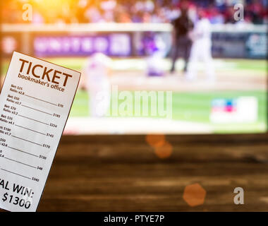 Bookmaker ticket on the background of a TV showing baseball, sports betting, bookmaker - Stock Photo