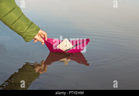 The girl is launching a red paper boat, close-up - Stock Photo