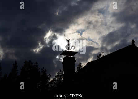A stuffed cat dummy sits on a chimney at home, thick black clouds and sun - Stock Photo