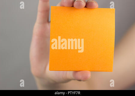 A female hand holds an orange clean sticker - Stock Photo