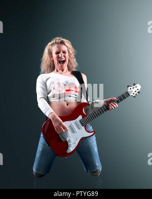 beautiful young blonde woman with a guitar sings a rock song - Stock Photo
