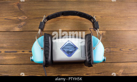 Audio player and headphones on a wooden background - Stock Photo