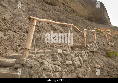 Stone steps with wooden handrails leading up to the top of a rocky mountain - Stock Photo