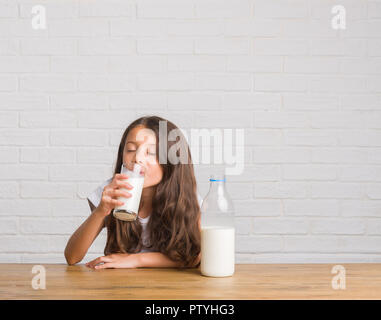 Young hispanic kid sitting on the table drinking a glass of milk with a confident expression on smart face thinking serious - Stock Photo
