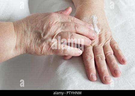 elderly woman rubbing hand cream, white background, close-up - Stock Photo