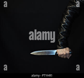 A man's hand in a jacket with a knife on a black background - Stock Photo