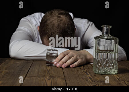 A drunk businessman lies on a table, in his hand a shot of wine with alcohol, a black background - Stock Photo