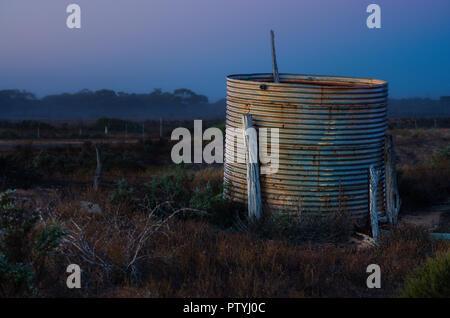 Rusted corrugated iron rainwater tank near old ruins on farm in early morning light near Ceduna South Australia