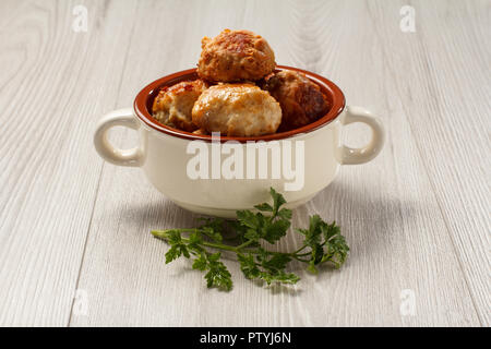 Fried meat cutlets in white ceramic soup bowl and branch of fresh parsley on grey wooden table - Stock Photo