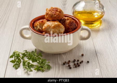 Fried meat cutlets in white ceramic soup bowl, glass bottle with sunflower oil, branch of fresh parsley and black peppercorn on grey table - Stock Photo