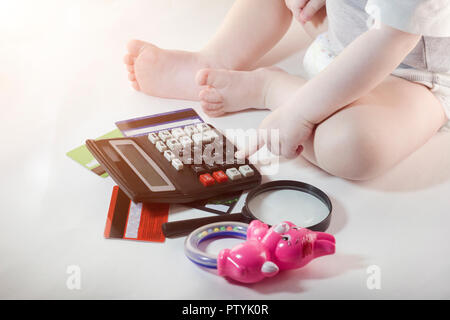 The child clicks on the calculator key, credit cards, white background - Stock Photo