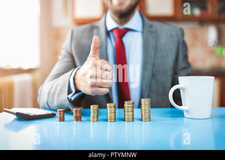 Working from home. Young businessman checking on returns from his investment - Stock Photo
