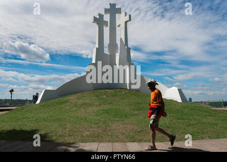 Three Crosses Hill, a tourist in Vilnius walks past three huge white crosses sited on a hill overlooking the city, Lithuania. - Stock Photo