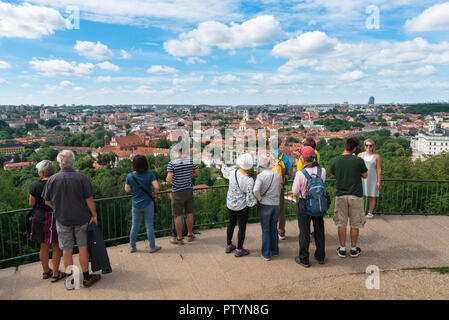 Tourism tourists Europe, on a summer day a group of tourists look down on the city of Vilnius from a viewing terrace on Three Crosses Hill, Lithuania. - Stock Photo